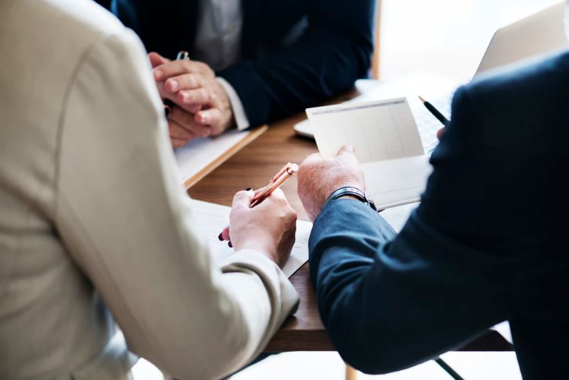 Two business men in a meeting, holding a checkbook ledger and discussing finances.