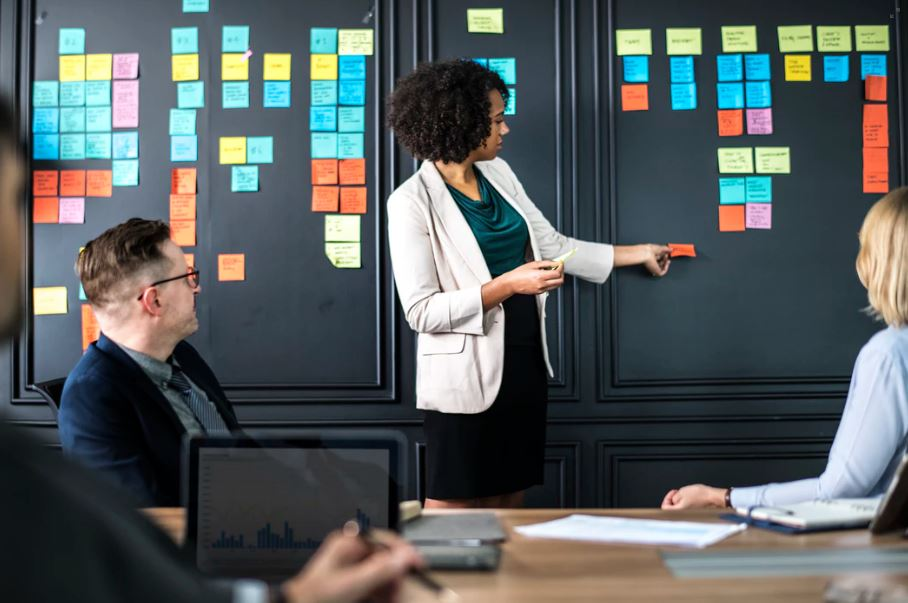 Woman standing in front of her team, moving post-it notes around on a meeting board.
