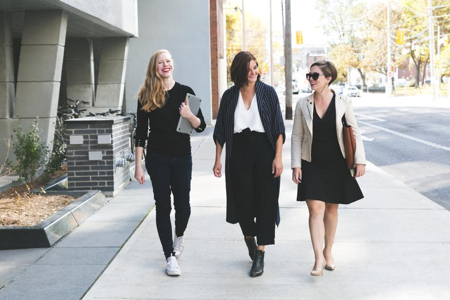 Three women dressed in business professional clothes walking and smiling with each other